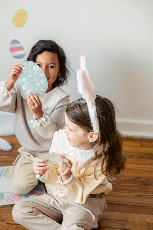 Cute diverse girls playing with Easter stickers on floor