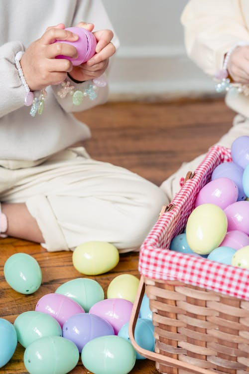 Crop faceless girls playing with many toy eggs