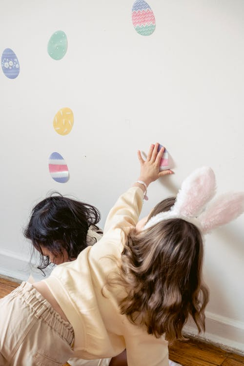 Unrecognizable little girls applying Easter stickers on wall