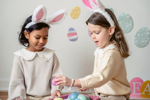 Content multiethnic girls in bunny ears playing with multicolored Easter eggs and sitting on floor in day care