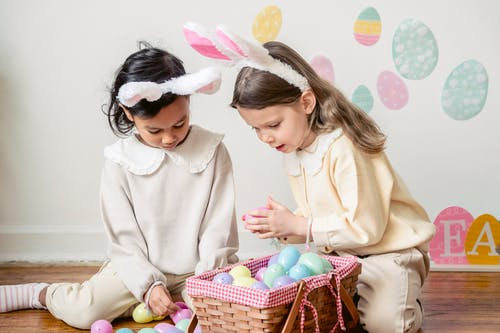 Content diverse girls playing with Easter eggs on floor