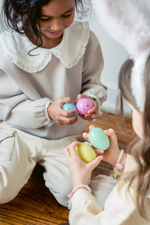 Positive multiethnic children playing with colorful Easter eggs at home