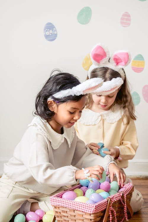 Adorable multiracial little kids in similar clothes and bunny ears choosing colorful egg toys from wicker basket during Easter Easter celebration at home