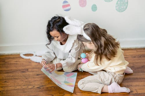 From above of concentrated little multiethnic friends in stylish clothes and bunny ears ripping stickers from paper sheet while decorating wall before Easter celebration