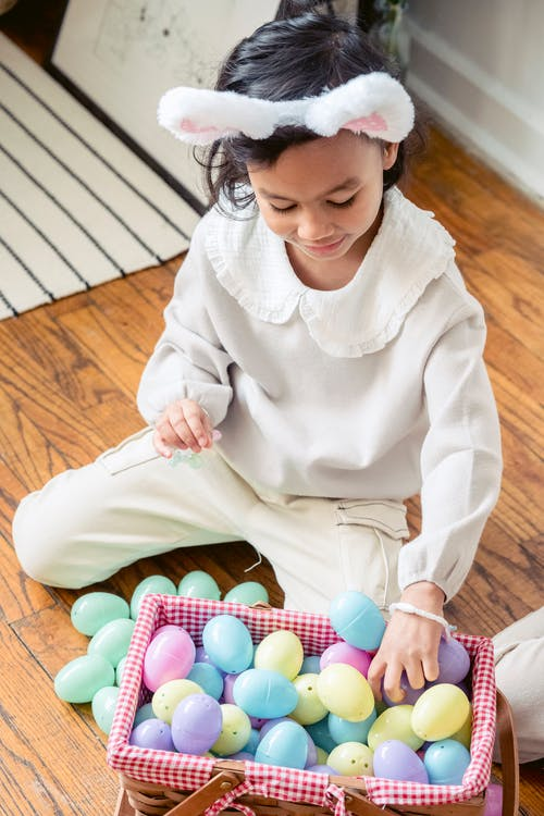 From above of adorable little Hispanic kid with bunny ears sitting on wooden floor and playing with colorful artificial Easter eggs placed in wicker basket