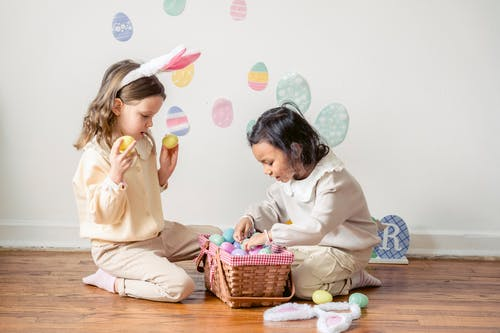 Side view of adorable little Hispanic girl choosing colorful Easter eggs while playing with friend on floor at home