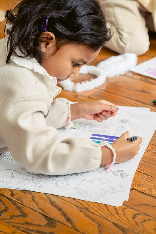 Side view of crop concentrated Hispanic little girl lying on wooden floor and drawing with crayon on paper