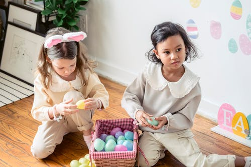 Calm diverse little girls playing with artificial Easter eggs sitting on floor in room