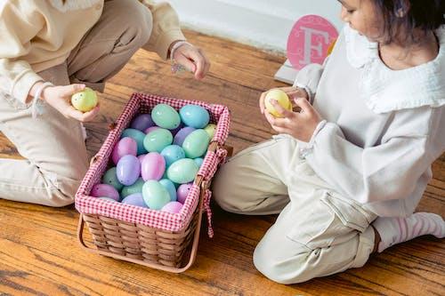 Multiethnic preschool funny girl sharing plastic eggs from basket