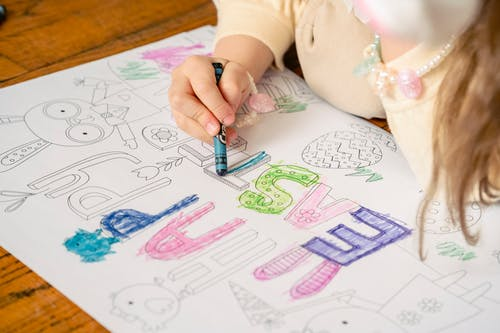 Girl coloring letters on greeting saying happy Easter