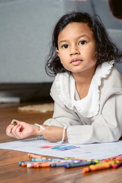 Little ethnic girl lying on floor and drawing