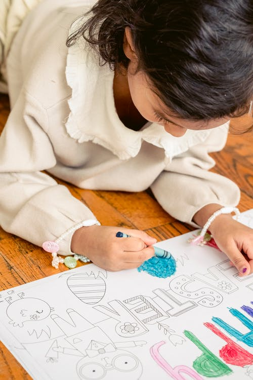 Concentrated little girl painting in coloring book at home