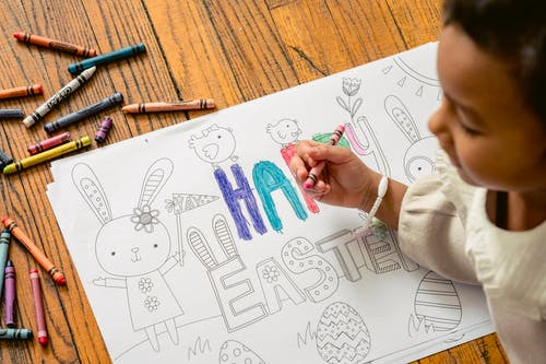 From above of crop ethnic girl painting in coloring book with Happy Easter inscription at home in daytime