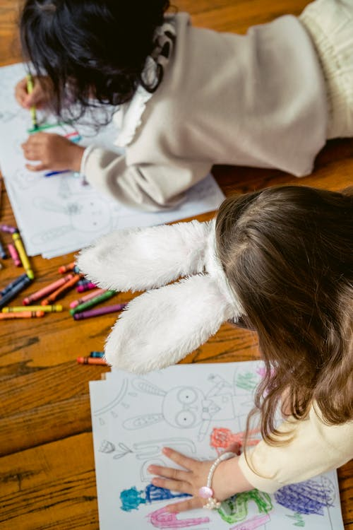 From above of crop faceless kids on wooden floor with wax pencil in hands coloring papers with Easter bunny and elements in light room