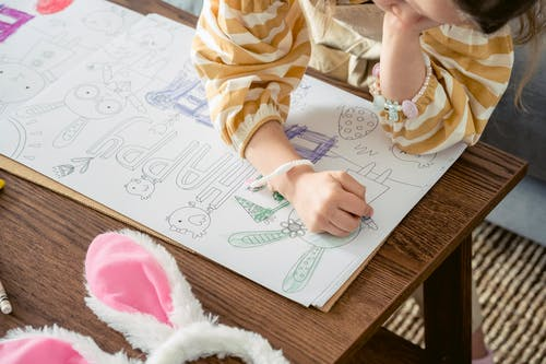 Girl coloring greeting poster for Easter party