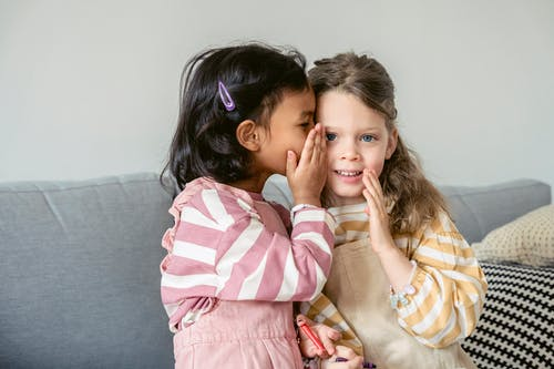 Ethnic girl sitting on sofa close to smiling best friend and whispering secrets on ear