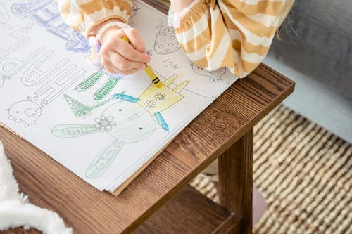 From above of crop anonymous little girl coloring bunny with colorful wax crayon on greeting poster for Easter