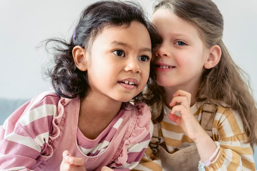 Smiling little Hispanic girl with brown eyes near cute best friend with long hair