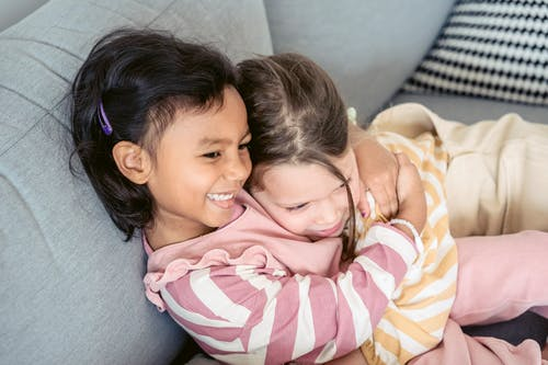 Cute diverse girls hugging tenderly on couch