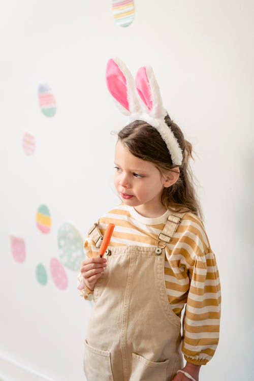 High angle of adorable preschool girl wearing bunny ears chewing peace of carrot while standing against white wall with Easter decor