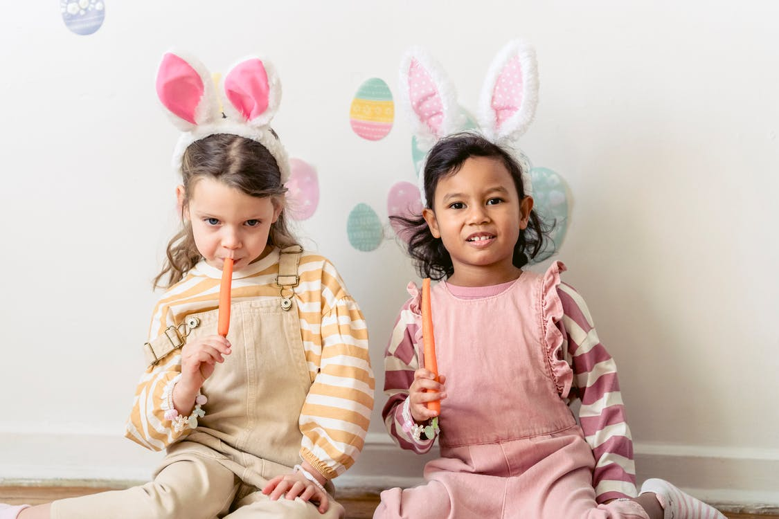 Multiethnic friends wearing similar festive outfits with rabbit ears eating carrots against wall with Easter egg shaped decor