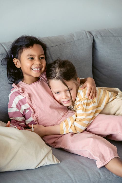 High angle of happy diverse girls caressing and embracing while sitting together on sofa