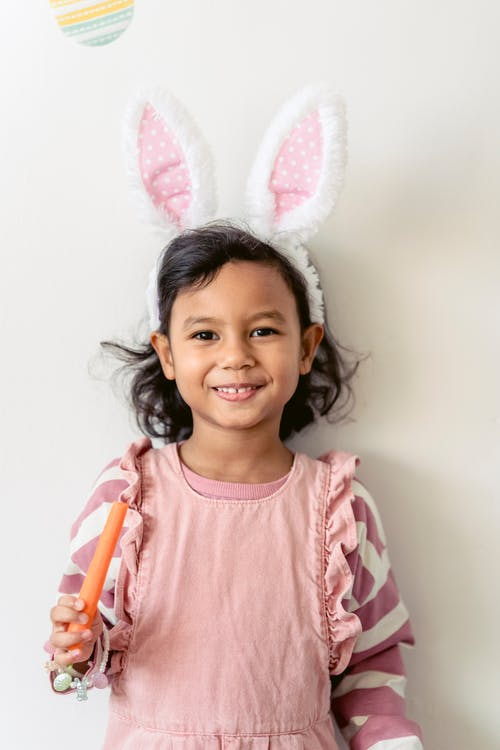 Adorable preschool girl wearing bunny ears for Easter celebration standing with carrot and smiling at camera