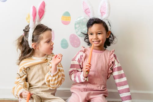 Adorable Hispanic girl with carrot sitting near friend in bunny ears against wall decorated with egg stickers