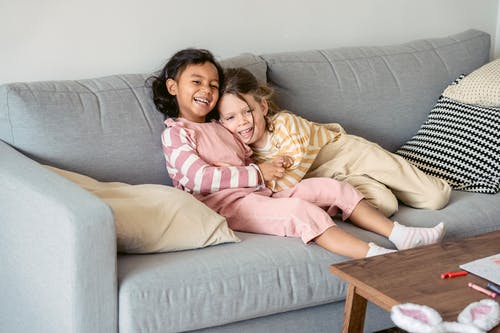 Cheerful multiethnic girlfriends wearing similar outfits cuddling on comfortable sofa at home near table with chalk pencils
