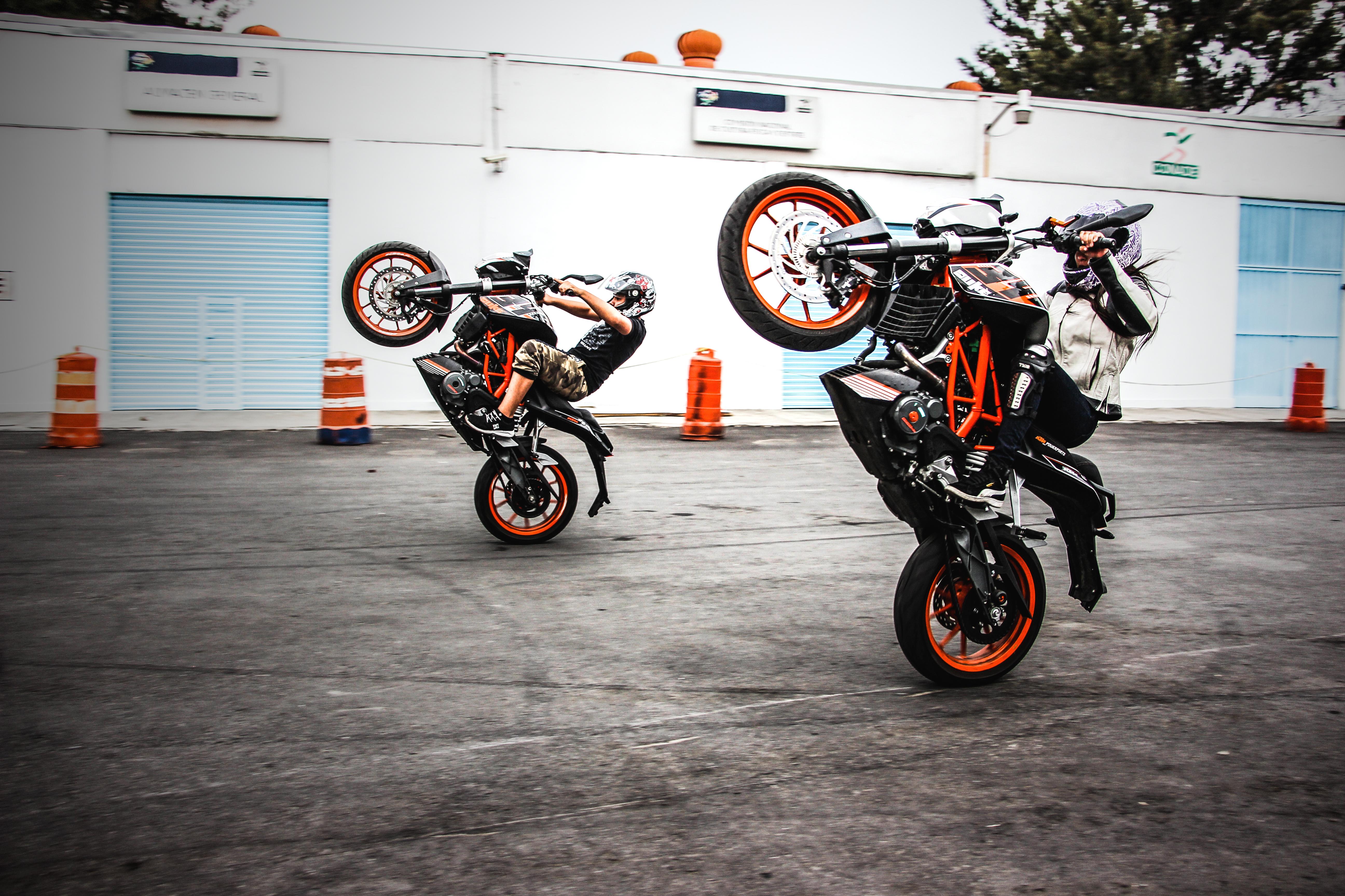 Two Men Riding Orange-and-black Sports Bikes While Doing Exhibition