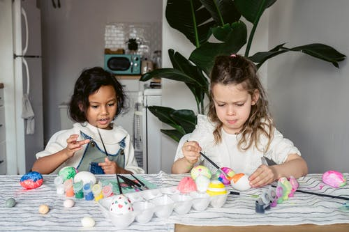 Concentrated multiracial girls painting white eggs with paintbrushes while sitting at table with paints in kitchen during Easter holiday at home