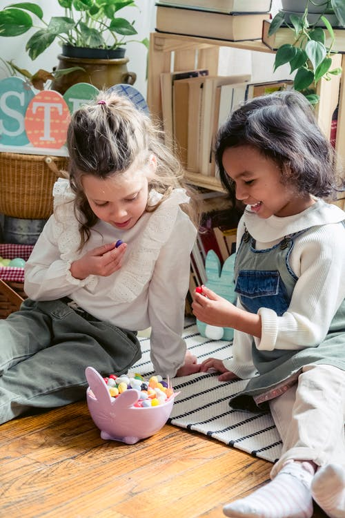 Positive multiracial girls sitting on floor together near bowl with small colorful eggs during Easter celebration in light room at home