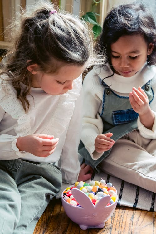 Concentrated multiethnic children sitting near bowl in shape of rabbit full of small decorative eggs during Easter celebration at home