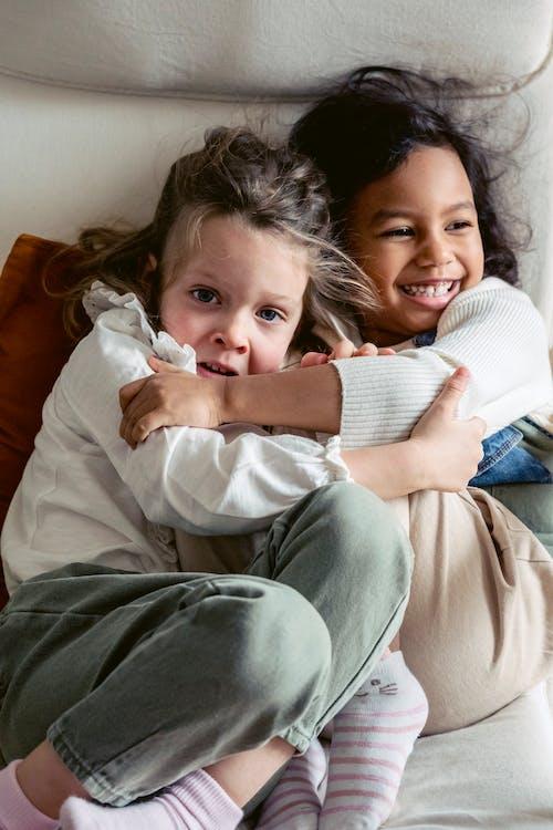 Cheerful diverse kids cuddling in room