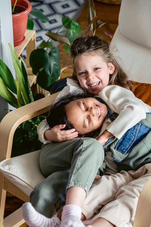 Cheerful multiethnic preschool children having fun while playing in white armchair in light room with green potted plants at home