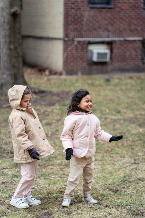 Cheerful Hispanic child with girlfriend in coat and gloves looking away on meadow in daytime