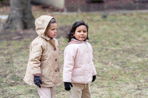 Multiethnic girls in outerwear on meadow in park