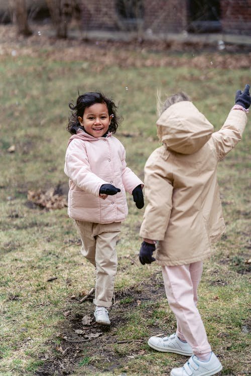 Smiling ethnic child looking forward while running against unrecognizable girlfriend in warm clothes on meadow under soap bubbles