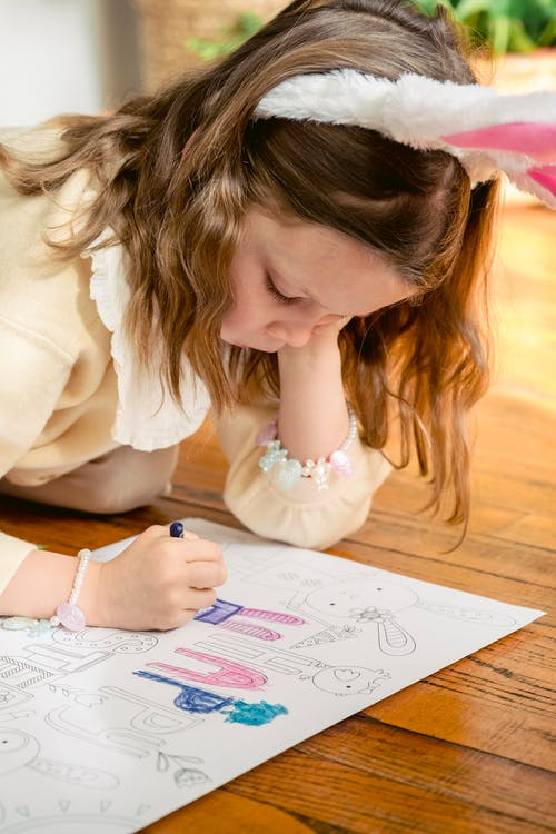Preschool child with bunny ears leaning on hand while coloring paper drawing on parquet during festive occasion in house