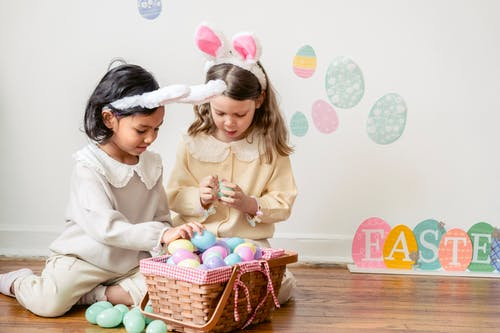 Best multiethnic friends sitting on parquet against basket with decorative eggs and Easter inscription at home