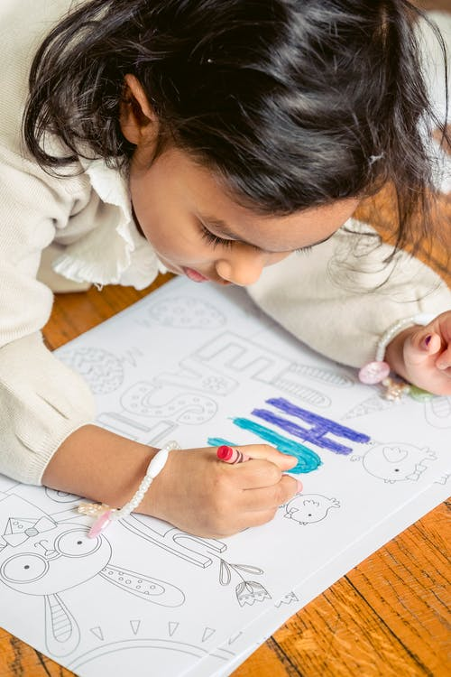 Crop ethnic girl coloring drawing on Easter Day