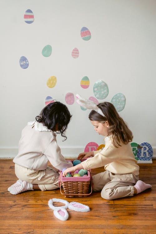 Side view of anonymous multiethnic kids sitting on floor with basket full of plastic eggs during festive event in house