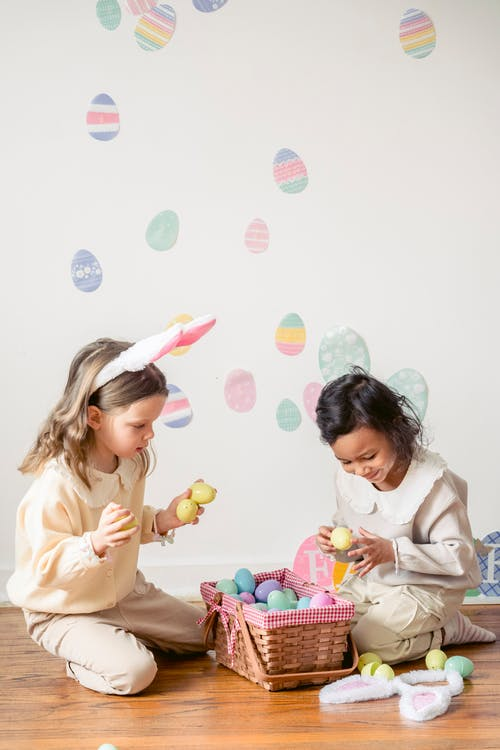 Charming girl with bunny ears sitting against smiling Hispanic child with decorative egg during festive occasion in house