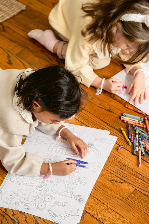 From above of crop focused multiracial children coloring paper drawings with crayons on parquet during festive occasion at home