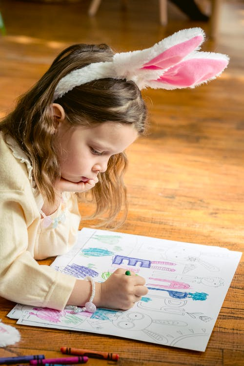 Charming girl with bunny ears coloring drawing on parquet
