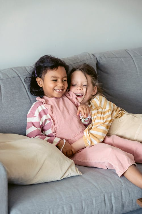 Cheerful child in striped wear embracing best ethnic friend while resting on sofa in living room