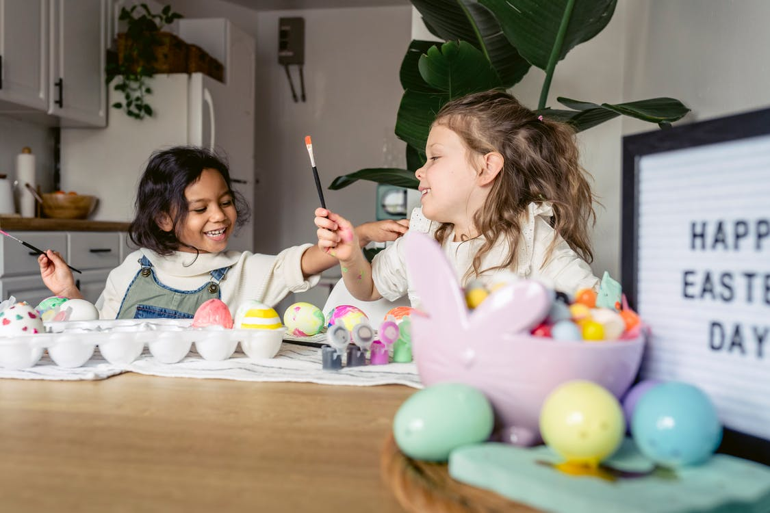 Smiling little multiracial kids in casual clothes sitting at wooden table and coloring Easter eggs with brushes and forms in light apartment