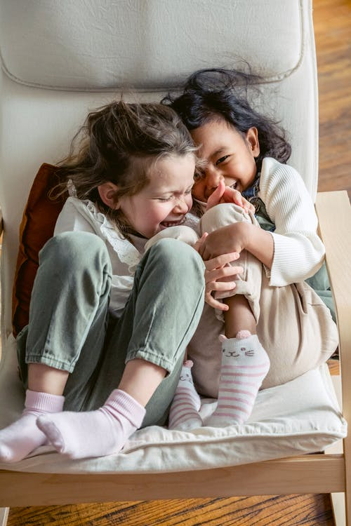 Adorable multiracial preschool girls laughing together while cuddling and sitting close on comfortable sofa