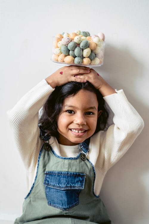 Indian girl smiling and looking at camera while holding bowl of colorful plastic Easter eggs on head on white background