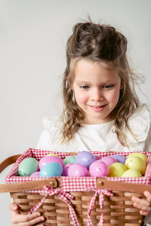 Adorable little girl looking at basket full of colorful plastic Easter eggs while standing on white background